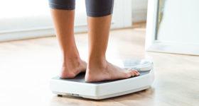 La prise de poids à la ménopause n'est pas une fatalité - photo d'une femme se pesant sur la balance