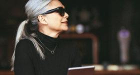 50 ans dans le vent - Pas d'âge pour les cheveux blancs - Image d'une femme de 50 ans avec des cheveux blancs en queue de cheval, dans un restaurant