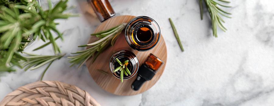On vous dit tout sur les huiles essentielles - Photo de plusieurs flacons d'huiles essentielles et branche de romarin