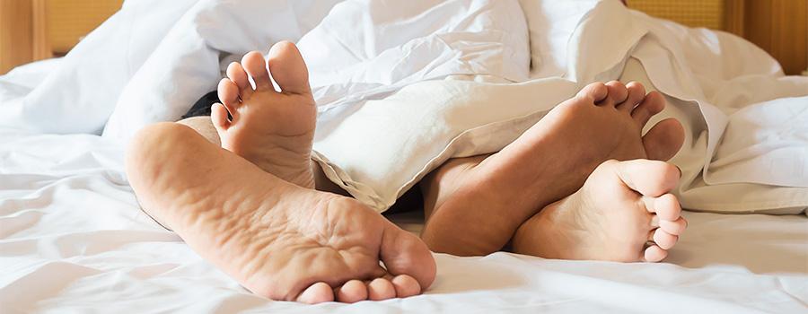 Sexe à 50 ans : Quels changements ? - Photo d'un couple sous la couette, les pieds qui dépassent