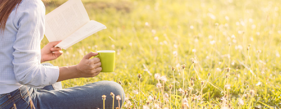 5 livres pour partir à la quête du bonheur - Femme assise dans un champs fleuri, en train de lire