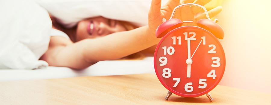 Bien dormir, la clé d'une bonne santé ! - Image d'une femme éteignant son réveil