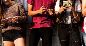 Nos ados : le dico de poche de leurs expressions - Photo d'une bande d'adolescents sur leur téléphone