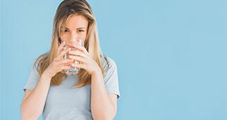 Quelle eau choisir et consommer ? - Photo d'une femme buvant un verre d'eau