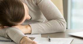 50 ans dans le vent - Article Plus jamais fatigué, c'est possible ? Photo d'une femme endormie, épuisée sur son bureau