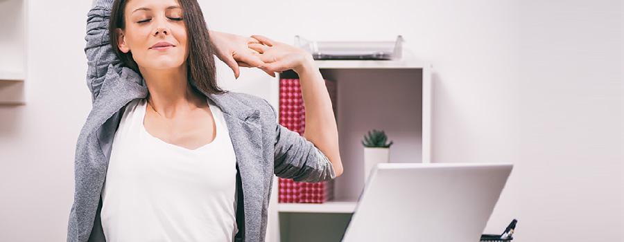 9 conseils pour éviter les douleurs lorsqu'on est assis devant son écran ou derrière un bureau - Image d'une femme faisant des étirements
