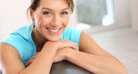 50 ans dans le vent - Rééducation du périnée et travail de la posture - Photo d'une femme souriante faisant des excercices pour le périnée sur une swissball